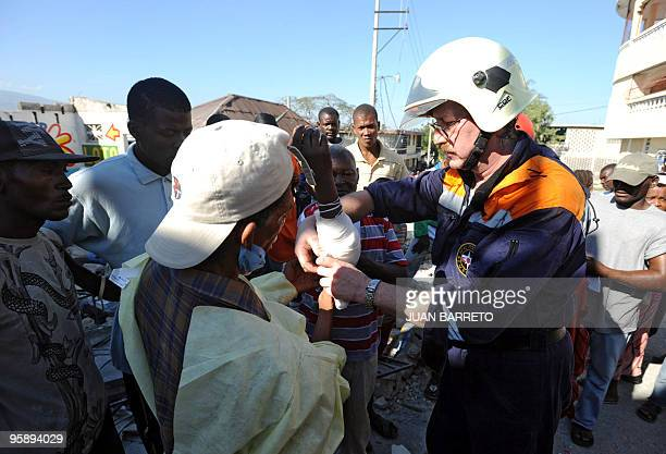 A member of the Russian rescue team bandages the forearm of an injured Haitian in PortauPrince January 15 2010 Despairing Haitians clawed by hand to...