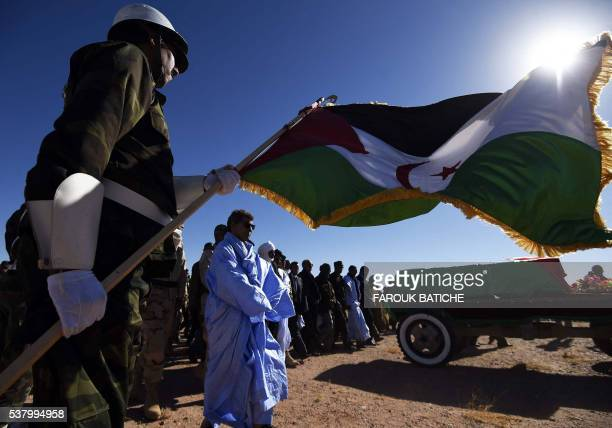 A member of the Sahrawi People's Liberation Army holds a flag of the disputed territory of Western Sahara during the funeral of Polisario Front's...