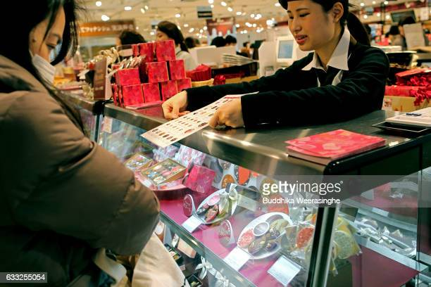 A member of the sales staff explains to a customer about Valentine's Day chocolate brands at a Hankyu Department Store on February 1 2017 in Osaka...