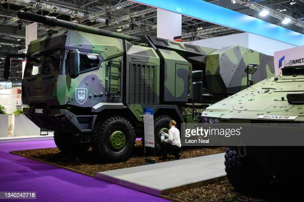 Member of the sales team cleans the wheels of a Rheinmetall HX10x10 truck based howitzer ahead of opening on day one of the DSEI exhibition at ExCel...