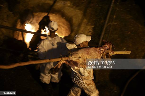 A member of the Samaritan community carries a slaughtered lamb during the traditional Passover sacrifice ceremony at Mount Gerizim near the northern...