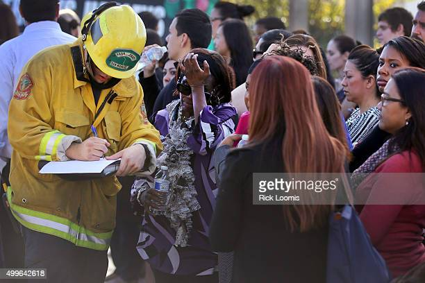 A member of the San Manual Fire Department takes the names of those being evacuated after a mass shooting at the Inland Regional Center on December 2...