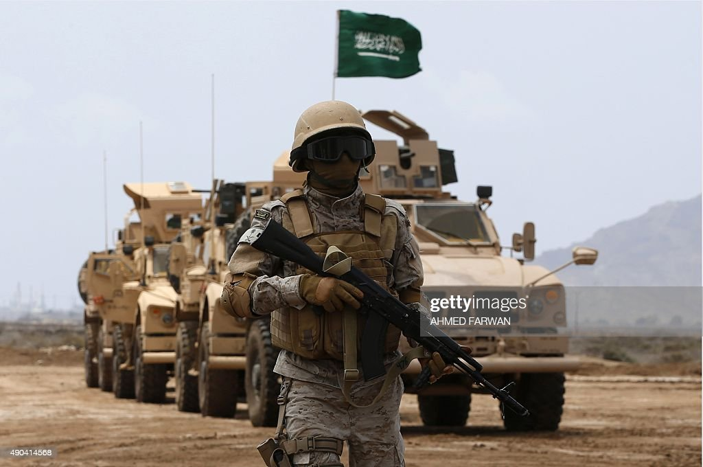 A member of the Saudi forces stands to attention during a visit by Yemeni Prime Minister Khaled Bahah at the Saudi-led coalition military base in Yemen's southern embattled city of Aden on September 28, 2015. Since Bahah's return from exile on September 16, 2015, his government is conducting the country's business from Aden, and is aiming to reinforce fighters supporting Yemeni President Abedrabbo Mansour Hadi, battling Shiite Huthi rebels in the central region.