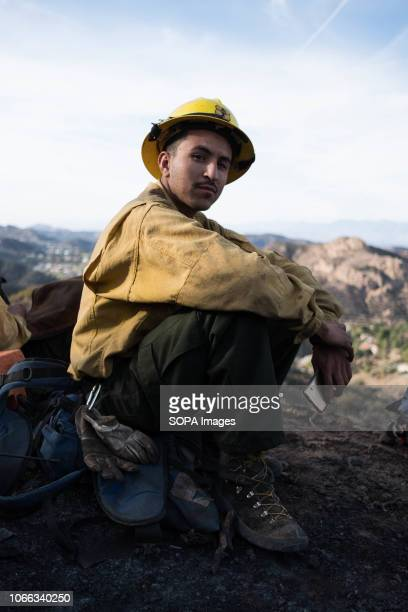 Member of The Scorpions is seen resting after tirelessly clearing breaks in brush in effort to stop Woolsey fire from spreading Woolsey Fire has...