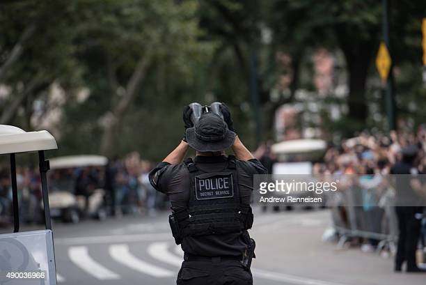 A member of the Secret Service checks roof tops before Pope Francis passes through Central Park on September 25 2015 in New York The pope is on a...