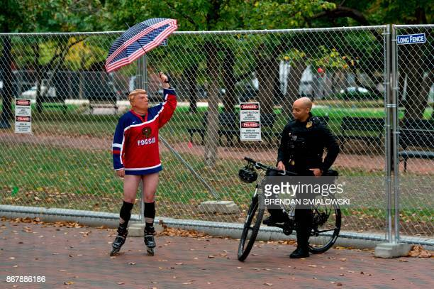 A member of the Secret Service looks at a man wearing a US President Donald Trump mask and a Russian hockey jersey staging a protest outside the...