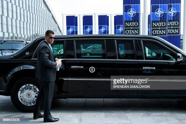 A member of the Secret Service polishes US President Donald Trump's armoured limousine 'The Beast' prior to his departure from NATO Headquarters in...