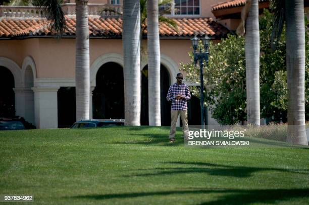 A member of the Secret Service stands guard as US President Donald Trump returns to MaraLago from the Trump International Golf Club on March 25 2018...