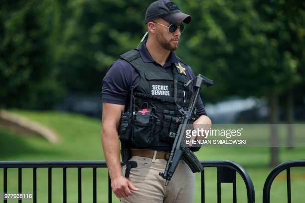 A member of the Secret Service stands guard near a road block on 17th Street near the White House on June 18 2018 in Washington DC