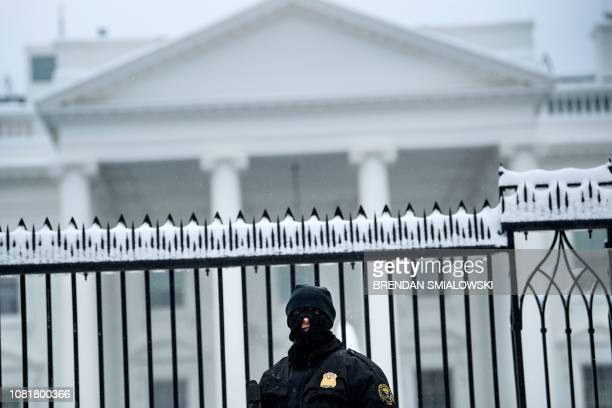 A member of the Secret Service stands guard outside the White House during the 23rd day of the US government shutdown January 13 2019 in Washington...