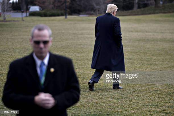 A member of the Secret Service stands watch as US President Donald Trump walks toward Marine One on the South Lawn of the White House in Washington...