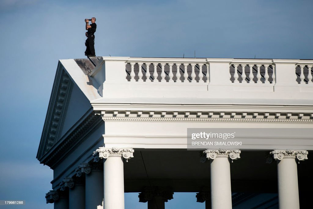 A member of the Secret Service's counter sniper team looks out from the roof of the North Portico of the White House September 7, 2013 in Washington, DC. AFP PHOTO/Brendan SMIALOWSKI