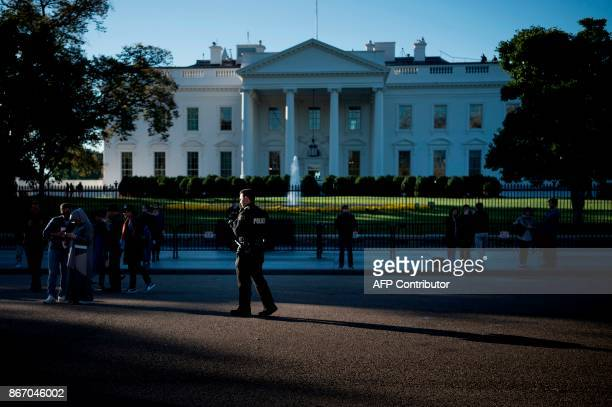 A member of the Secret Service's uniformed division patrols Pennsylvania Avenue in front of the White House on October 27 2017 in Washington DC / AFP...