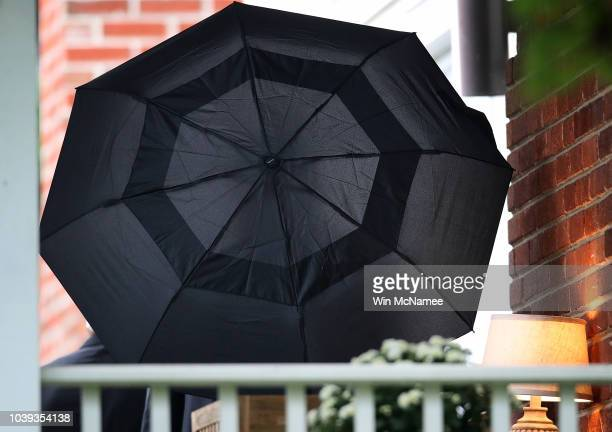 A member of the security detail assigned to Supreme Court nominee Brett Kavanaugh uses an umbrella to obscure the veiw of Kavanaugh leaving his home...