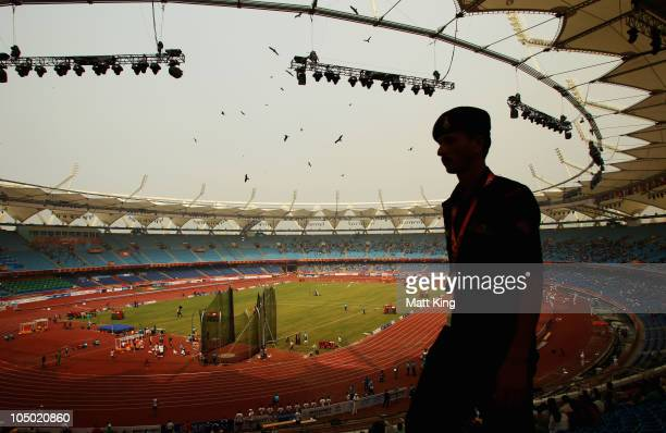 Member of the security force patrols the interior of the stadium as athletes compete in front of empty stands at the Jawaharlal Nehru Stadium during...