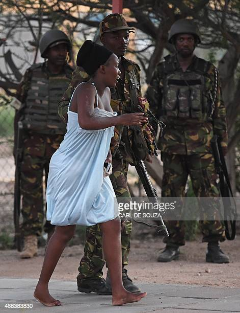 Member of the security forces escorts a student out of a Kenyan University campus in Garissa on April 2 after an attack by Somalia's Al-Qaeda-linked...