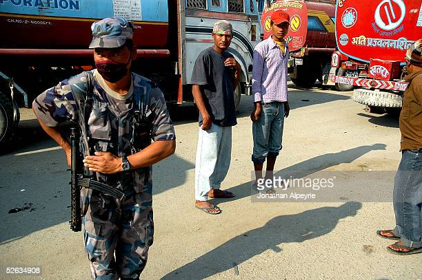 A member of the security forces salutes a passing lieutenant as trucks drivers look on February 27 2005 in the eastern Terai district of Hetauda...