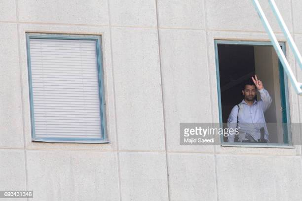 A member of the security forces shows a V sign at a window in Iran's parliament building following an attack by several gunmen on June 7 2017 in...