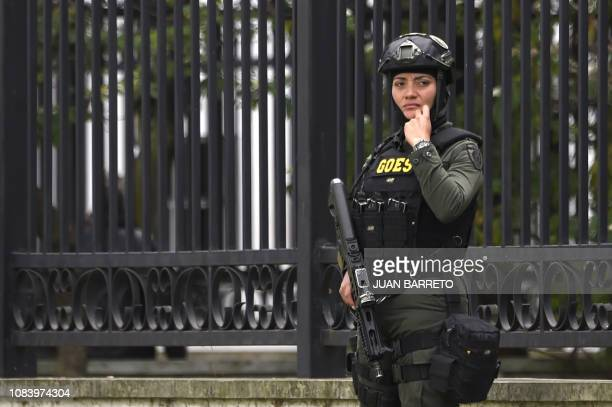 A member of the security forces stand guard at the site of an explossion on a police cadet training school in Bogota on January 17 2019 The Colombian...