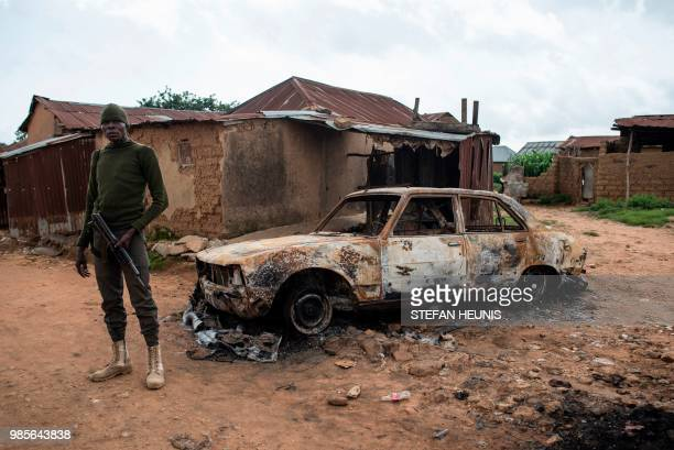 A member of the security forces stands next to a burnt out vehicle in the Nghar Village near Jos on June 27 after Fulani herdsmen attacked the...