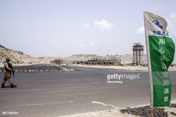A member of the security forces walks through a development site operated by China Overseas Ports Holding Co near Gwadar Port in Gwadar Balochistan...