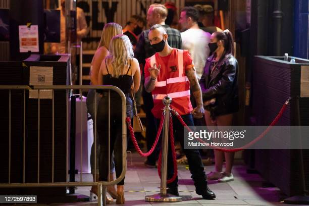 Member of the security staff at Coyote Ugly bar wears a face covering as he speaks to two women at the entrance to the bar on September 13, 2020 in...