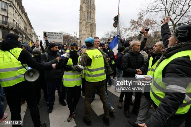 A member of the security team of the gilets jaunes movement wearing a white armband faces a demonstrator during an antigovernment demonstration...