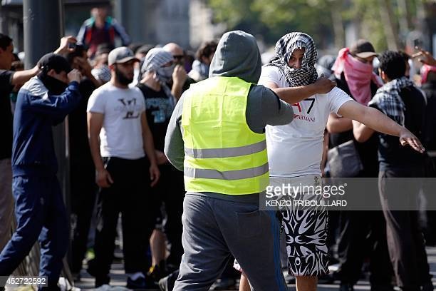A member of the security team of the proPalestinian supporters speaks with a man doing the quenelle gesture on the Republique square in Paris during...
