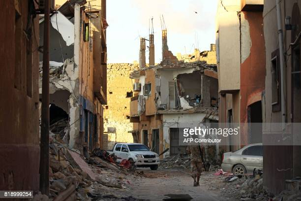 A member of the selfstyled Libyan National Army loyal to the country's east strongman Khalifa Haftar walks through a heavily damaged street in...