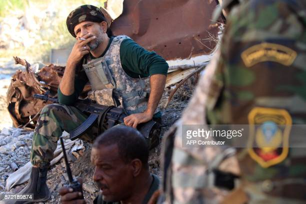 A member of the selfstyled Libyan National Army loyal to the country's east strongman Khalifa Haftar smokes a cigarette as he rests while sitting on...