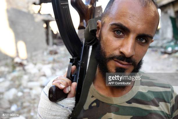A member of the selfstyled Libyan National Army loyal to the country's east strongman Khalifa Haftar poses with a Kalashnikov assault rifle as he...