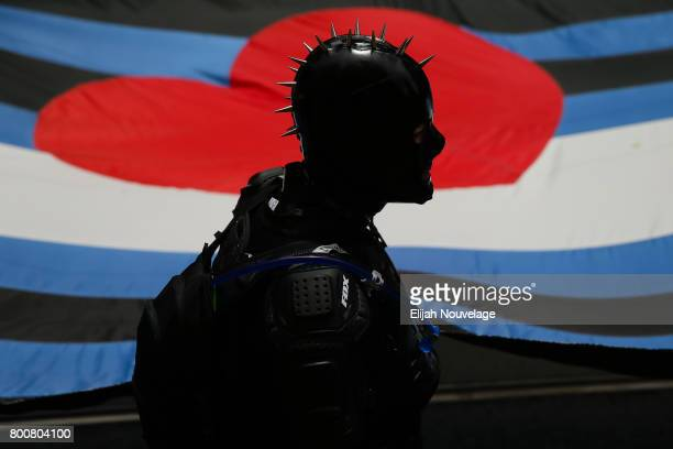 A member of the SF Leather contingent is silhouetted against a large flag while participating in the annual LGBTQI Pride Parade on June 25 2017 in...