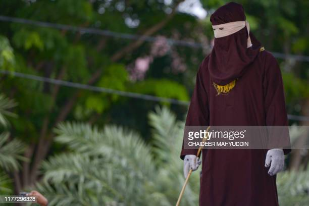 A member of the Sharia police waits before a public caning in Banda Aceh on October 21 2019 Despite international condemnation public flogging is a...