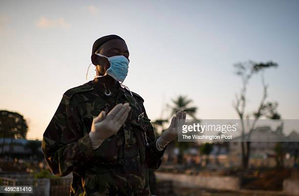 A member of the Sierra Leone military says a prayer as bodies are buried at King Tom Cemetery in Freetown Sierra Leone on Wednesday November 19 2014...