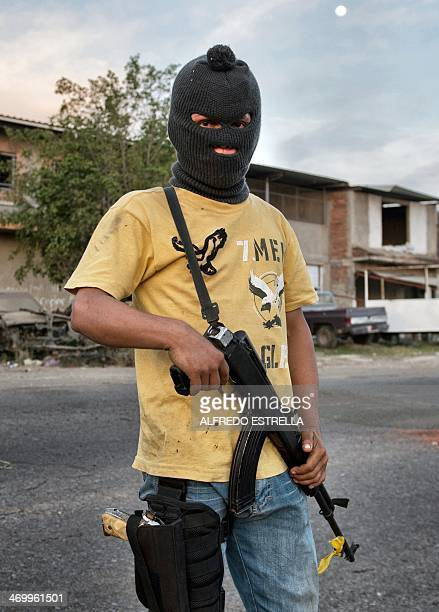 A member of the socalled selfdefense groups poses for a photo with a Kalashnikov assault rifle in Apatzingan Michoacan state Mexico on February 12...