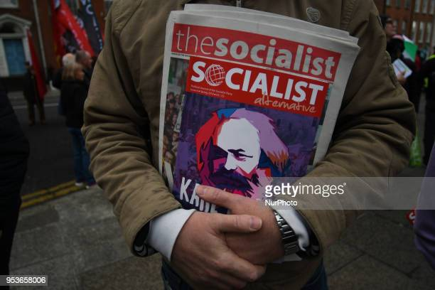 A member of the Socialist Party holds a latest Socialist Alternative paper as Hundreds of people including SIPTU unions Right2Work campaigners...