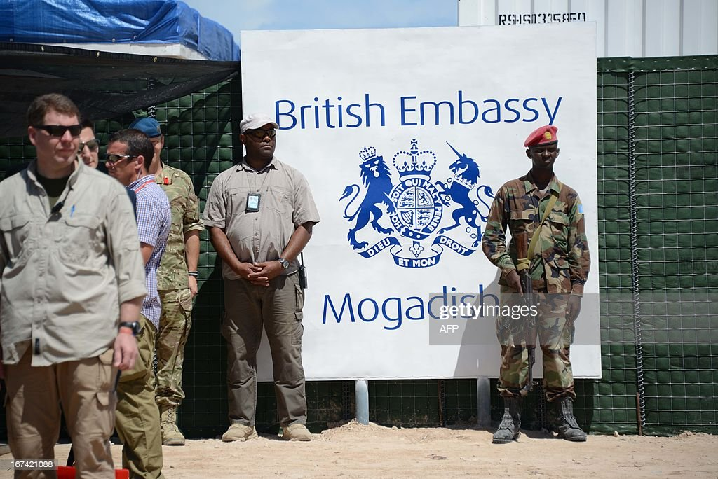 A member of the Somali military stands next to the sign of the newly opened British Embassy in Mogadishu on April 25, 2013. British Foreign Secretary William Hague opened a new embassy in Mogadishu on April 25, 22 years after London pulled its diplomats from conflict-torn Somalia. AFP PHOTO / Mohamed Abdiwahab