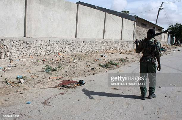 A member of the Somali security forces looks at blood stains on the ground following a bomb blast in Mogadishu on August 3 2014 At least three city...