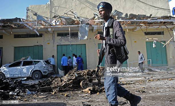 A member of the Somali security forces stands guard at the site of a bomb blast near Makka alMukarama Road in Mogadishu on December 19 2015 Several...