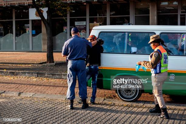 A member of the South African Police Service gets hold of a taxi driver during a police roadblock in the Johannesburg CBD on March 27 2020 South...