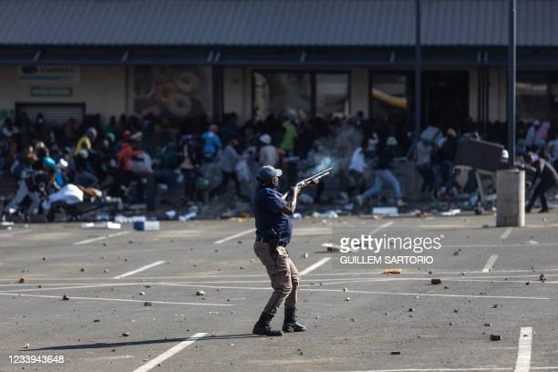 Member of the South African Police Services fires rubber bullets at rioters looting the Jabulani Mall in Soweto, southwest of Johannesburg, on July...
