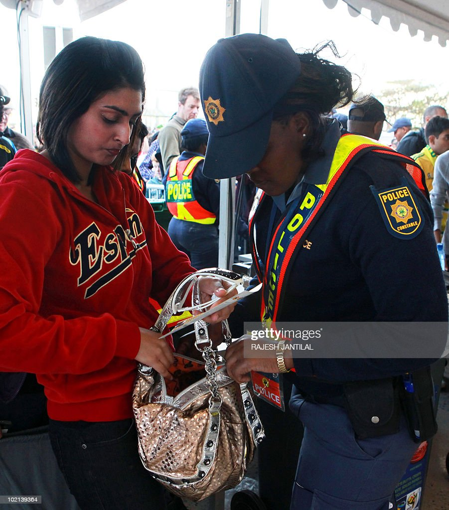 A member of the South African Police Services (SAPS) searches the purse of a football fan at a gate of Moses Mabhida stadium in Durban, South Africa, on 16 June 2010 before the start of the 2010 World Cup match between Switzerland and Spain. The SAPS have taken over security at World Cup stadiums in Durban and Cape Town after private security guards went on strike over their wages.