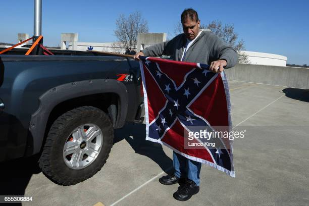 A member of the South Carolina Secessionist Party prepares to fly a Confederate battle flag in a parking garage beside the Bon Secours Wellness Arena...