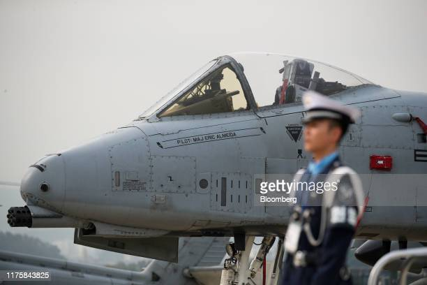 A member of the South Korean Air Force stands in front of the US Air Force Fairchild Republic A10 Thunderbolt II jet during media day at the Seoul...