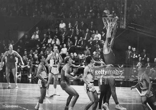 A member of the Soviet Union team attempts to ward off an American attack during play in the final of the basketball tournament at the 1964 Summer...