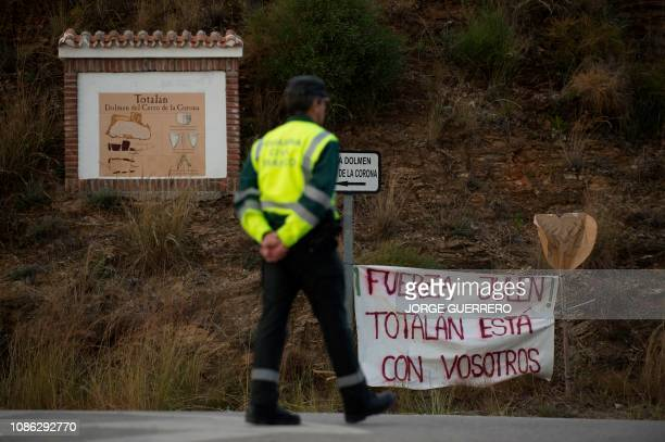 A member of the Spanish Guardia Civil stands near a barnner reading Be strong Julen Totalan is with you at the site where a child fell down a well in...