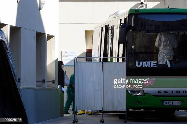 Member of the Spanish Military Emergencies Unit transfert a patient into a bus used to transport patients from the Gregorio Maranon Hospital to a...