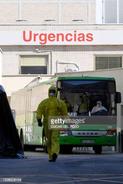 A member of the Spanish Military Emergencies Unit wearing protective walks in front of a bus used to transport patients from the Gregorio Maranon...