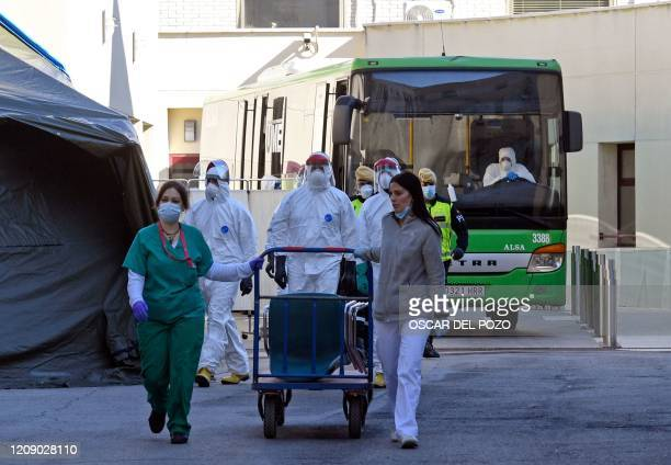 Member of the Spanish Military Emergencies Unit wearing protective suits and healthcare workers walk in front of a bus used to transport patients...