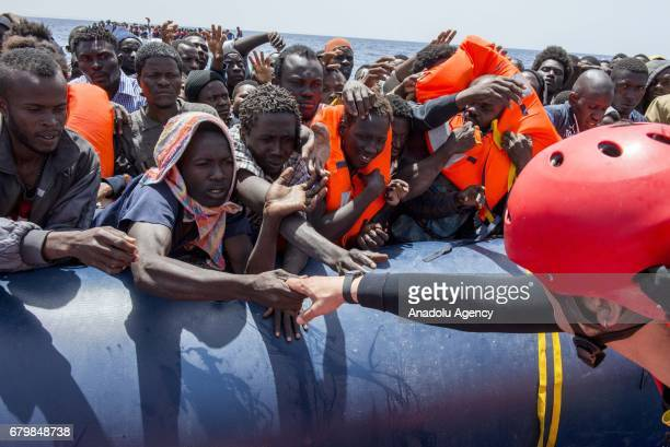 A member of the Spanish NGO Pro Activa gives a hand to the people during a rescue in the Mediterranean Sea Italy on May 06 2017 Iker Pastor / Anadolu...